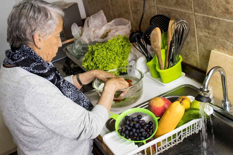 Midsection of woman standing by fruits at home
