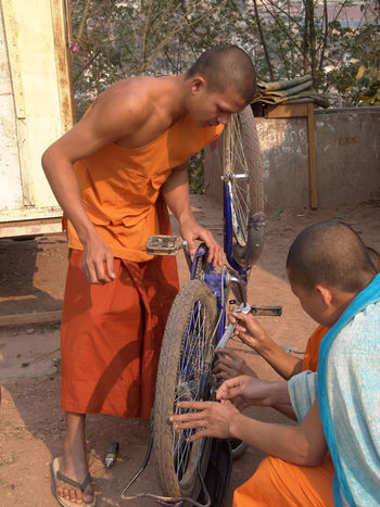 Fixing Buddha's bike Bicycle Repair Boys Casual Clothing Day Laos Leisure Activity Lifestyles Men Monks Orange Robes Outdoors Real People Shirtless Togetherness Two People Young Adult