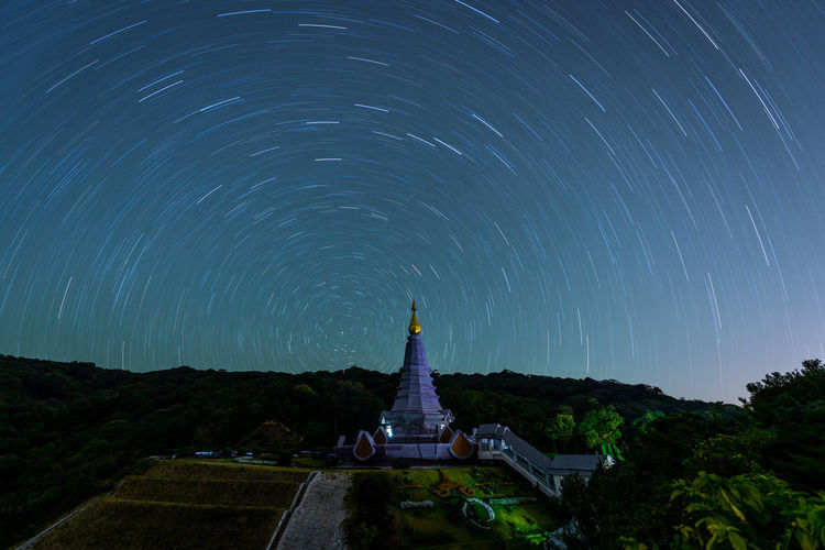 Temple against star trails at night