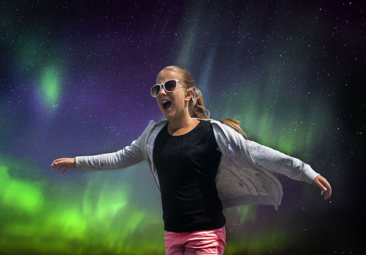 Low angle view of girl wearing sunglasses screaming while standing against northern lights