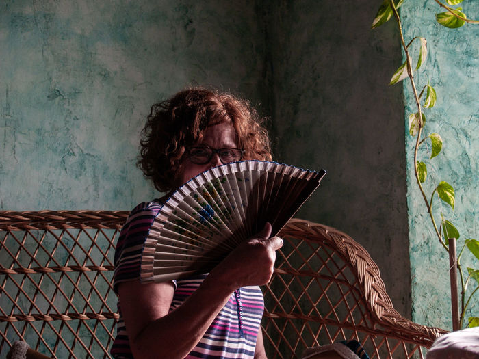 Portrait Of Woman Covering Face With Hand Fan At Home