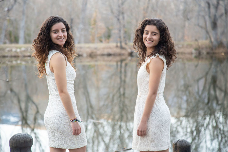 Portrait of smiling sisters wearing white dresses while standing by lake