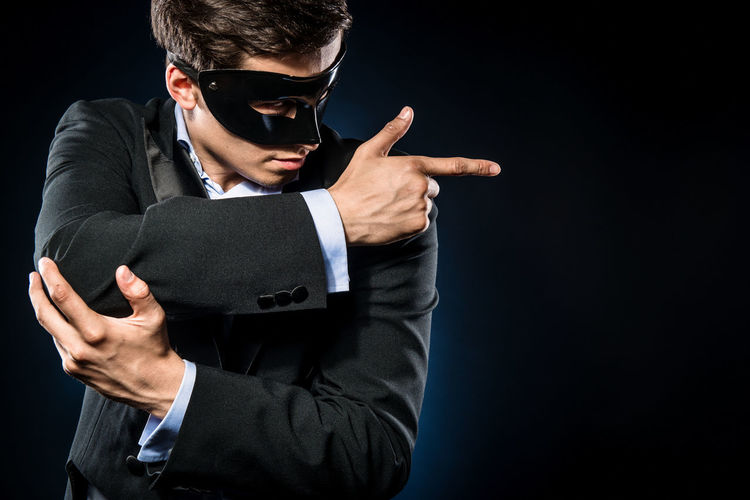 Man in mask gesturing while standing against black background