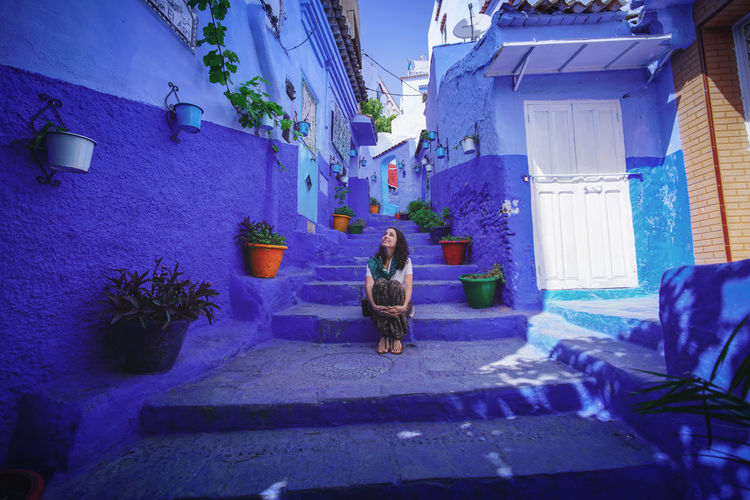 """""""The Blue City"""" - Deep in blue Chefchaouen Chefchaouen Medina Chefchaouen Blue City Morocco Travel Destinations Travel Travel Photography Digital Nomad Tourism Tourist Attraction  Tourist Destination EyeEmNewHere EyeEm Best Shots Architecture Built Structure Building Exterior One Person Women Sitting Building Lifestyles Real People Plant Adult Leisure Activity Staircase Nature Rear View House Full Length Blue Residential District Alley"""