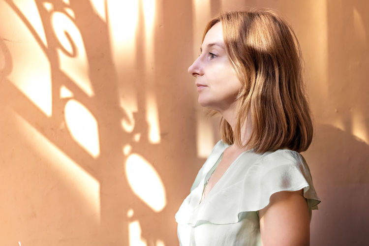 Portrait of a young woman in profile with red hair against the background of a wall with shadows