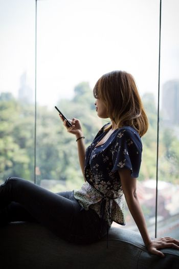 Side View Of Woman Using Phone While Sitting By Window