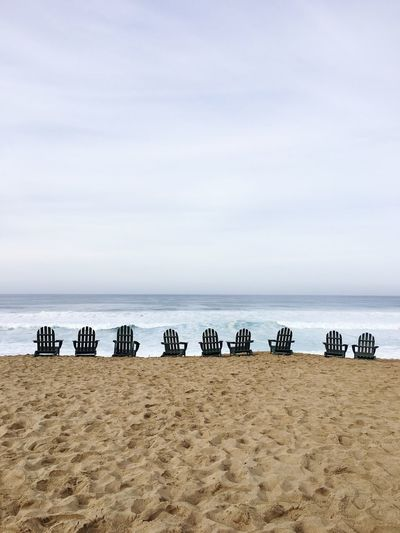 Empty adirondack chairs at beach against sky