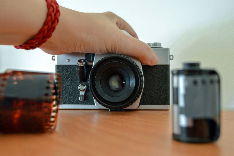 Cropped hand holding camera at table