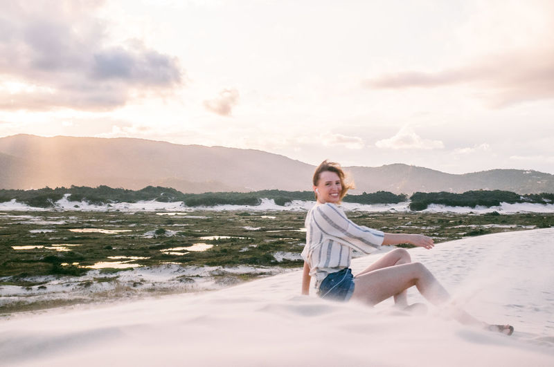 Beach Beauty In Nature Brasil Dunes Florianópolis Full Length Looking At Camera Mountain Nature One Person Outdoors Portrait Real People Sand Sand Dune Scenics Sea Sky Smiling Sun Sunlight Sunset Water Young Adult Young Women