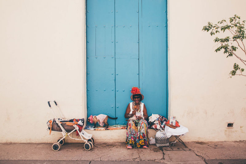 Full length of woman sitting by toy building