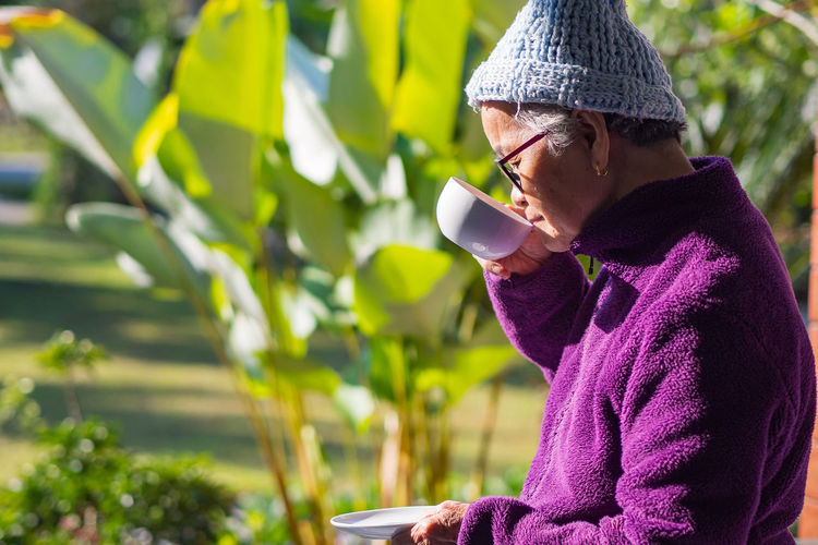 Elderly woman standing drink coffee from white coffee cup in the garden