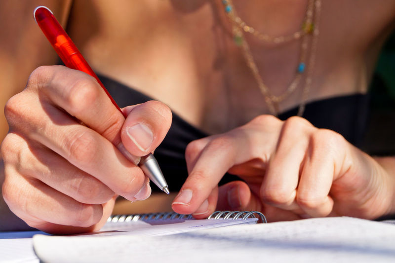 Midsection of woman writing on note pad