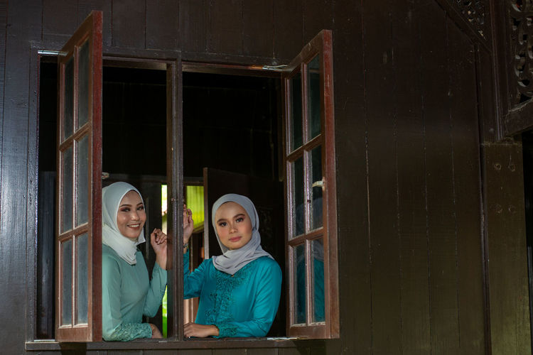 Portrait of two muslim women by the window in a malay wooden house.