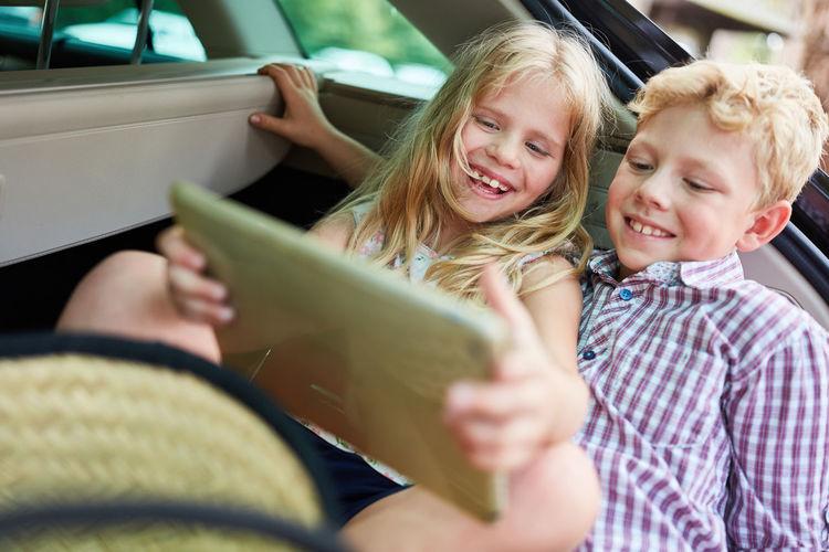 Happy siblings using digital tablet in car trunk