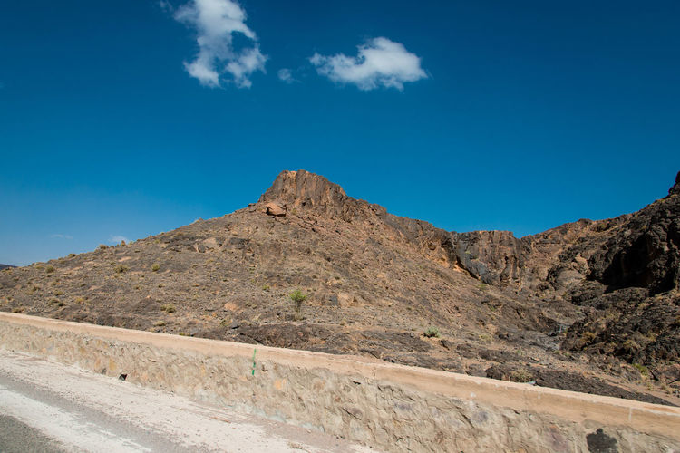 Scenic view of road and mountains against blue sky