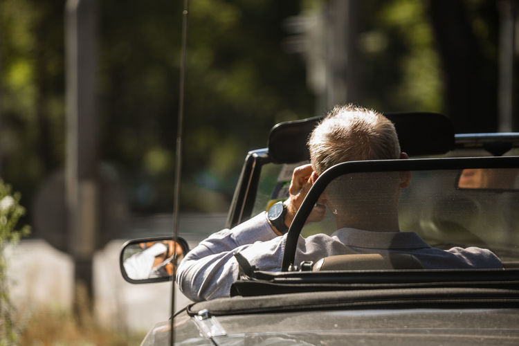 Rear View Of Man Sitting On Car