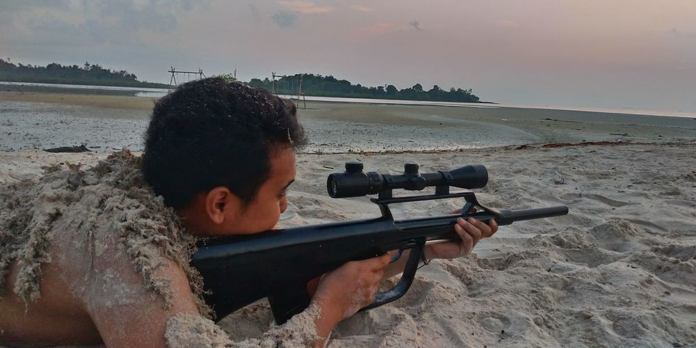 Side View Of Shirtless Young Man Aiming Rifle While Lying On Sand Against Sky During Sunset