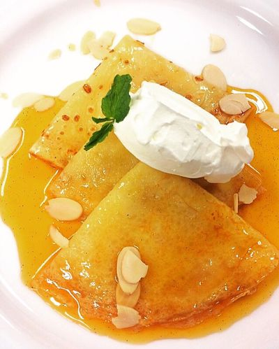 Crêpe Suzette is a French dessert consisting of a crêpe with beurre Suzette, a sauce of caramelized sugar and butter, tangerine or orange juice zest. Scratchbaking Plateddessert Caramel Plate Table Food Porn Food Photography Food Taking Pictures Ready-to-eat EyeEm Dessert Porn Dessert Serving Size