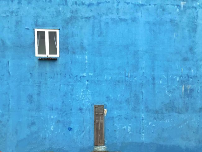 Small door and window in a blue building Minimalist Architecture Blue Wall Window Small Door Blue Built Structure Architecture Day No People Outdoors Building Exterior The Graphic City