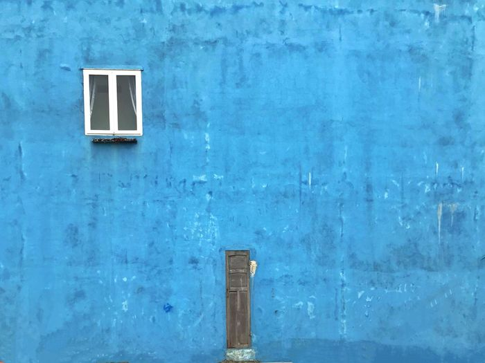 Small door and window in a blue building Minimalist Architecture Blue Wall Window Small Door Blue Built Structure Architecture Day No People Outdoors Building Exterior The Graphic City The Minimalist - 2019 EyeEm Awards