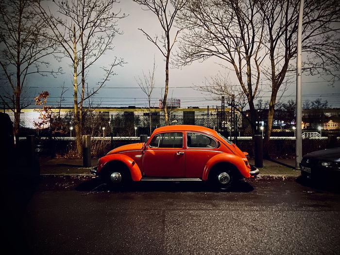 Car on wet street against sky in city