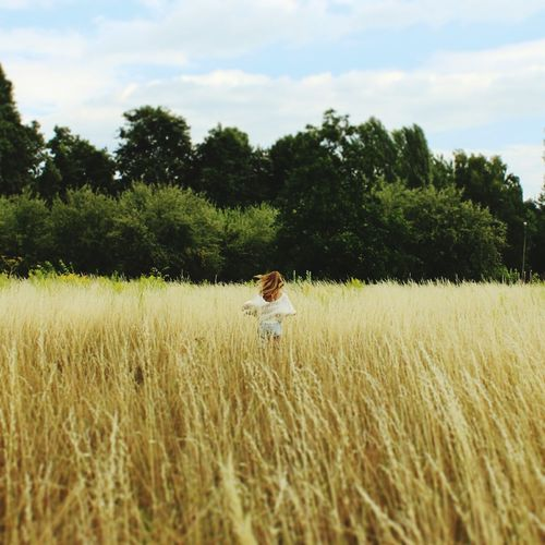 Rear view of woman running in field against sky