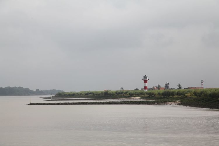 Lighthouse on field by elbe river against cloudy sky