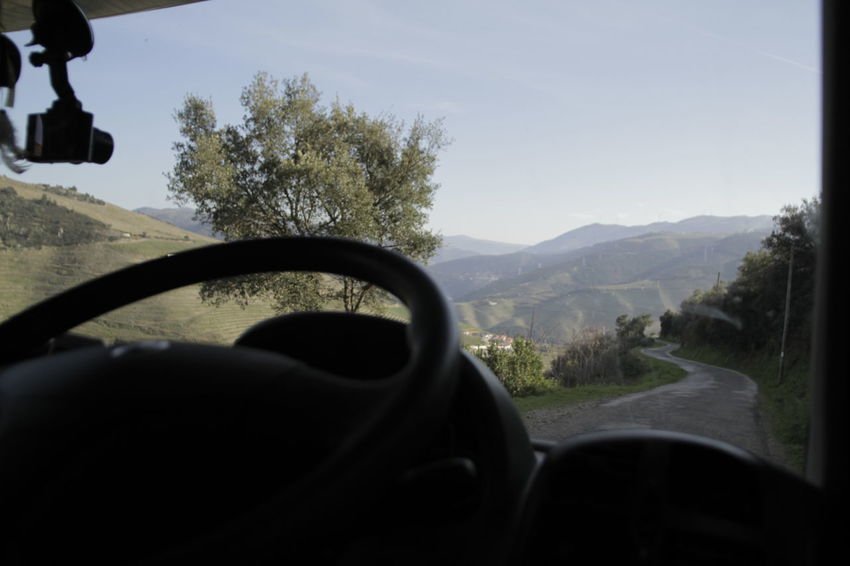 Looking through windscreen at mountain path Beauty In Nature Car Car Interior Close-up Day Human Hand Land Vehicle Landscape Mode Of Transport Mountain Nature One Person Outdoors People Real People Road Sky Steering Wheel Transportation Tree Vehicle Interior Windshield