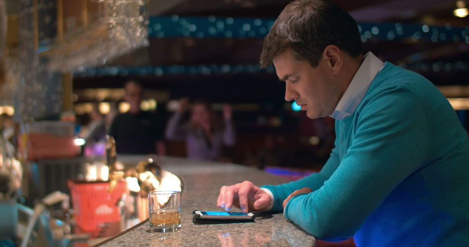 Side view of man using smart phone while sitting on table