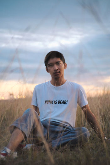 Portrait of young man sitting on grassy land against sky at sunset