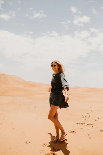 Woman Walking On Desert In Sunny Day