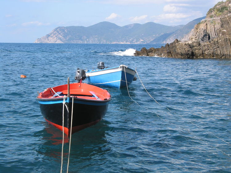 Two colourful boats in blue sea, mountains in the background. Cinque Terre, Italy Blue Sea Boats And Water Day Mountain Nature Nautical Vessel No People Outdoors Sea Water