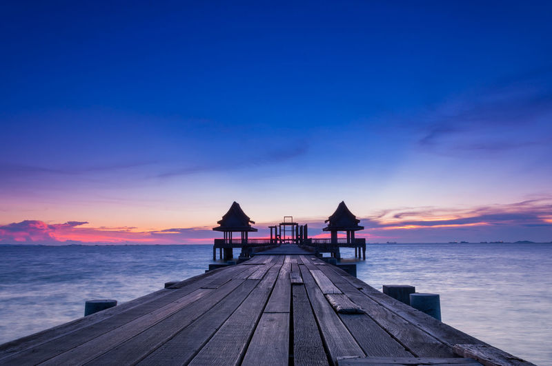 Pier at sea against sky during sunset