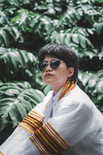 Woman wearing sunglasses while sitting against plants