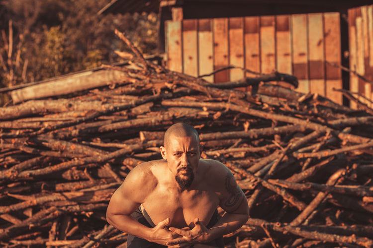 Portrait of shirtless man lying on field