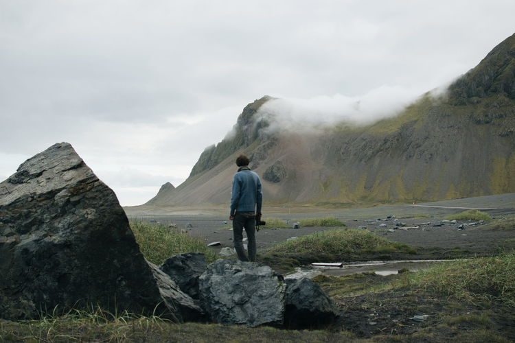 One Person Mountain Real People Full Length Leisure Activity Sky Beauty In Nature Lifestyles Scenics - Nature Non-urban Scene Rock Solid Rock - Object Rear View Men Cloud - Sky Outdoors Standing Black Beach Iceland A New Beginning Redefining Menswear