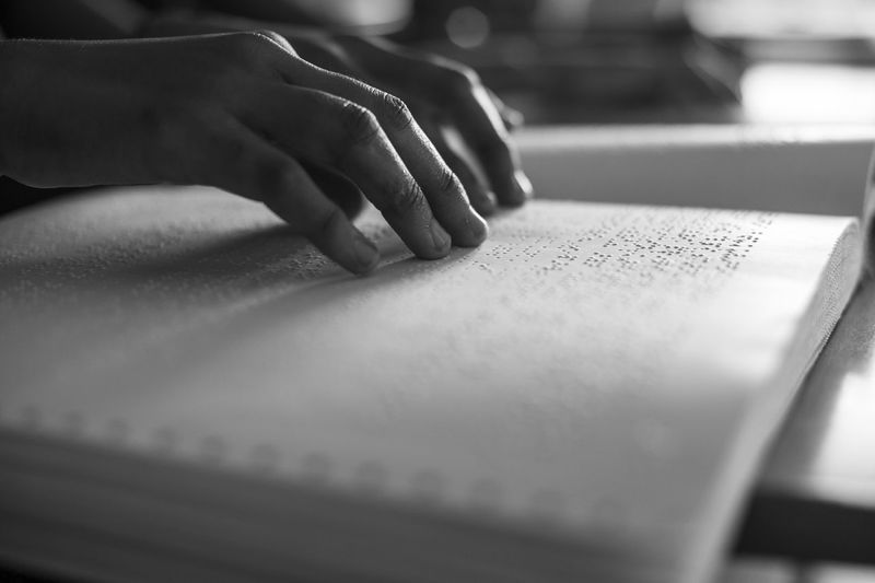 Cropped image of person reading braille