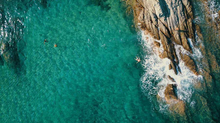 Beauty In Nature Day High Angle View Leisure Activity Lifestyles Nature Outdoors Real People Rock Rock - Object Rock Formation Scenics - Nature Sea Solid Sport Swimming Turquoise Colored Water Waterfront
