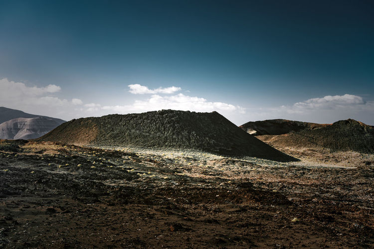 Collapsed volcanic cone in a dark field of multicolored basalt ashes