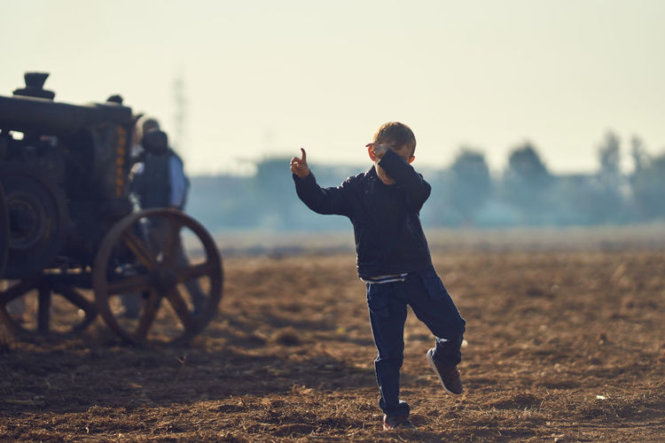 Boy dancing on dirt field