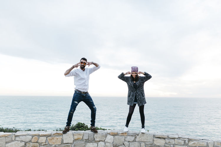 Full length of couple gesturing while standing on retaining wall against sea