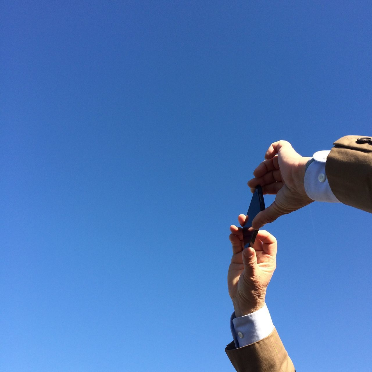 Close-up of hands photographing clear blue sky