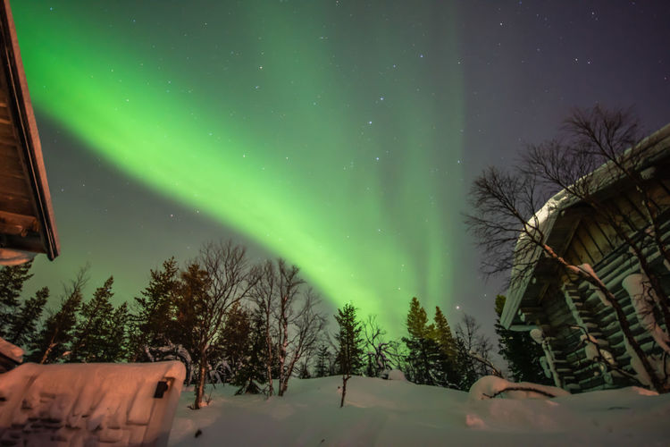 Low Angle View Of Aurora Borealis In Sky Seen From Snow Covered Field
