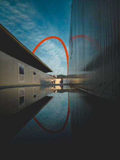 Digital composite image of swimming pool by building against sky