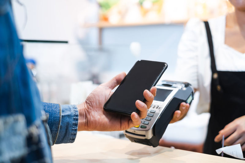 Midsection of man using phone while paying at caf�