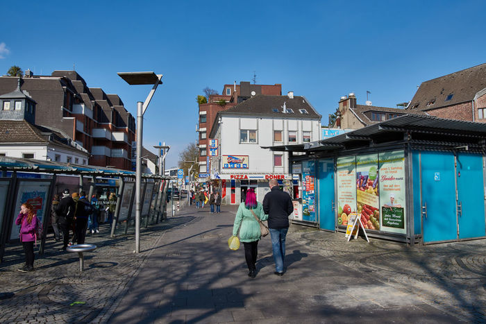 Moenchengladbach, Germany - March 09, 2016: Pedestrants enjoy the sun while strolling over the Old Market of Moenchengladbach which is known for bars, restaurants, and boutiques Blue Sky Building City Downtown Mönchengladbach Pedestrant Soccer Street Photography Stretview
