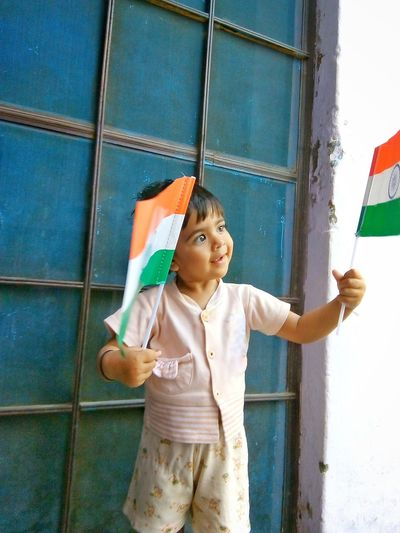 indian child holding national flag of India Holding Hand Flag Flags National Nation Nationalism Patriotic Patriotism Looking At Flag Kid Girl Portrait Treditional Indian Indian Culture  Smiling Babygirl Boy Little Child Childhood Standing Girls Closed Door Gap Toothed Innocence Babyhood Cute Asian Ethnicity Love Is Love