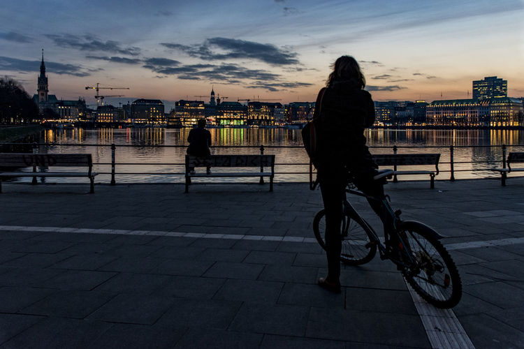 Man with bicycle on river in city at sunset