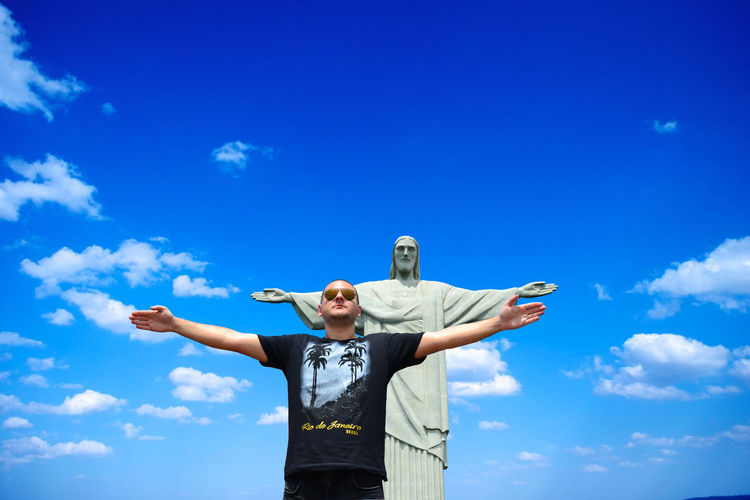 Low angle view of man with arms outstretched standing against christ the redeemer