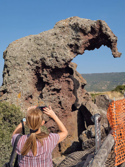 Rear view of woman looking at rock formation against clear sky